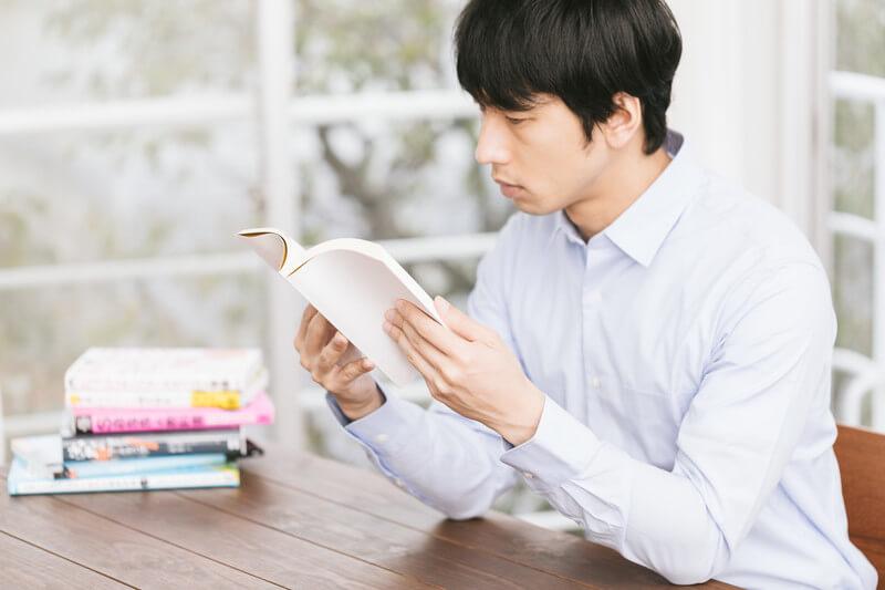 本を読むYシャツ姿の男性