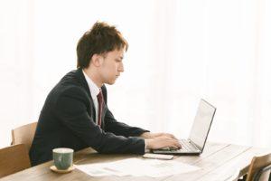 ノートパソコンに向かうスーツ姿の男性
