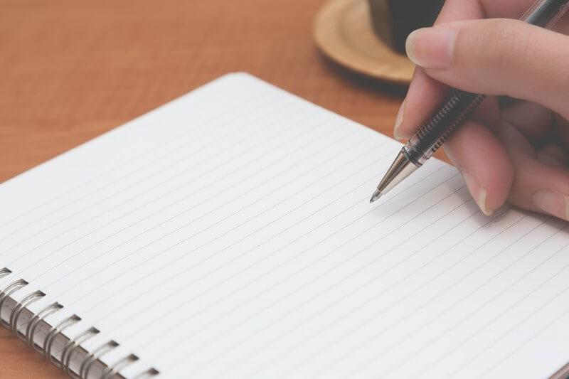 ボールペンでノートに書こうとする様子
