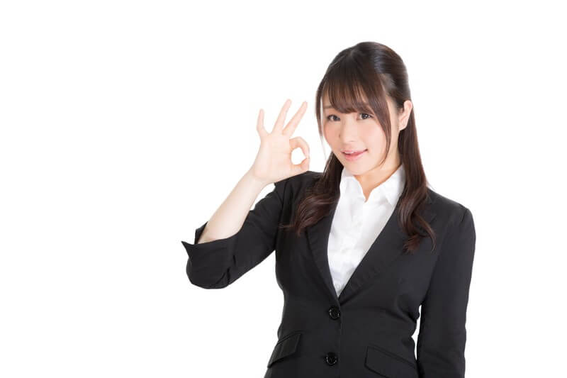 右手でOKサインを作るスーツ姿の女性