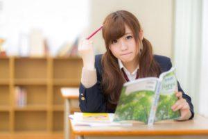 シャーペンを頭に当て勉強する女子生徒