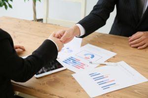 書類の上で握手をするビジネスパーソン