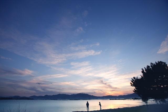 夜明けの水辺に佇む2人の人