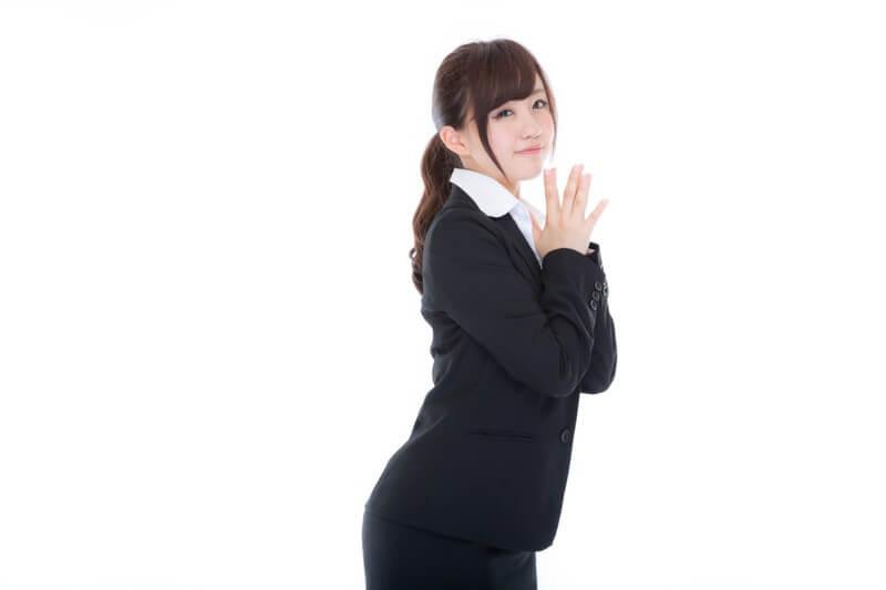 両手を合わせるスーツ姿の女性