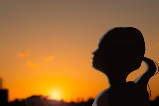 夕陽を背景に佇む女性