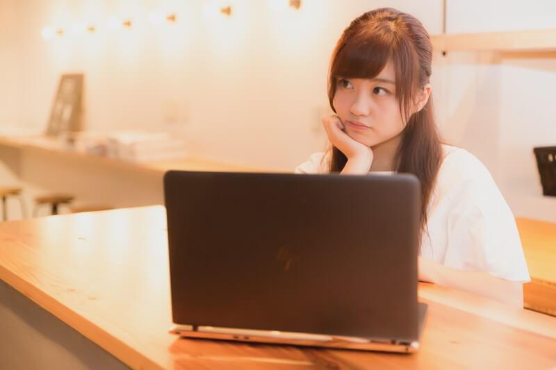 ノートパソコンの前で頬杖をつく女性