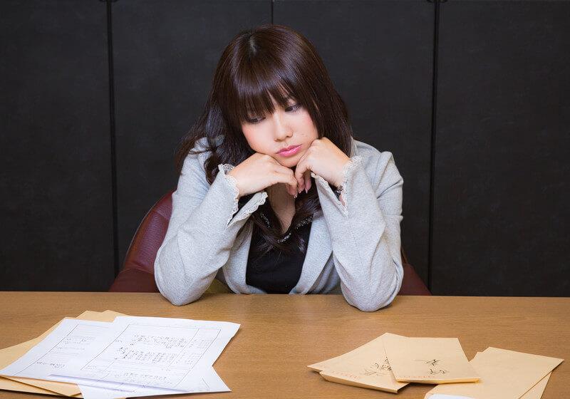 履歴書と辞表を前に頬杖をつく女性