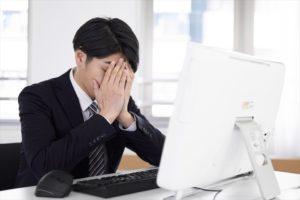 パソコンの前で落ち込むスーツ姿の男性