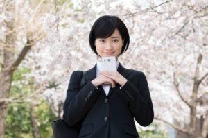 桜の木の下で胸元にスマホを抱える就活生