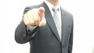 右人差し指を前に差すスーツ姿の男性