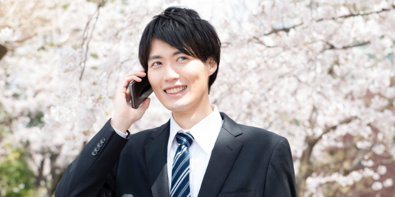 桜の下で電話をする男性