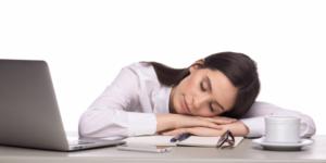 机にうつ伏せで寝る女性
